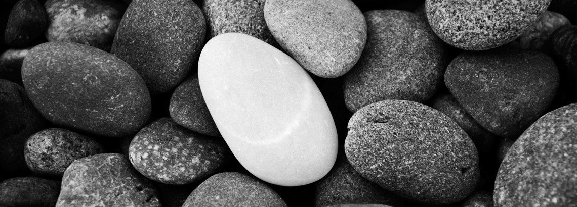 Single pale grey pebble among multiple dark grey pebbles