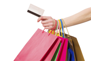 hand holding payment card and shopping bags