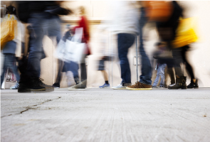 Blurred photographic image, taken from a low angle, of shoppers walking along a pavement