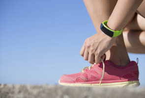 close up photo of a runner tying their shoelace with a fitness wearable on their wrist
