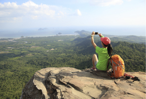 Woman with a rucksack sitting on a rocky ledge taking a picture of the view over forests below her to the distant sea