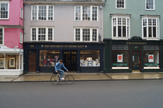 Photo – student cycling along a road in front of University of Oxford Bookshop. Oxford as Student Destination: TIWIS team's field trip to Oxford, May 2015. Photographer: Mahmut Bolat