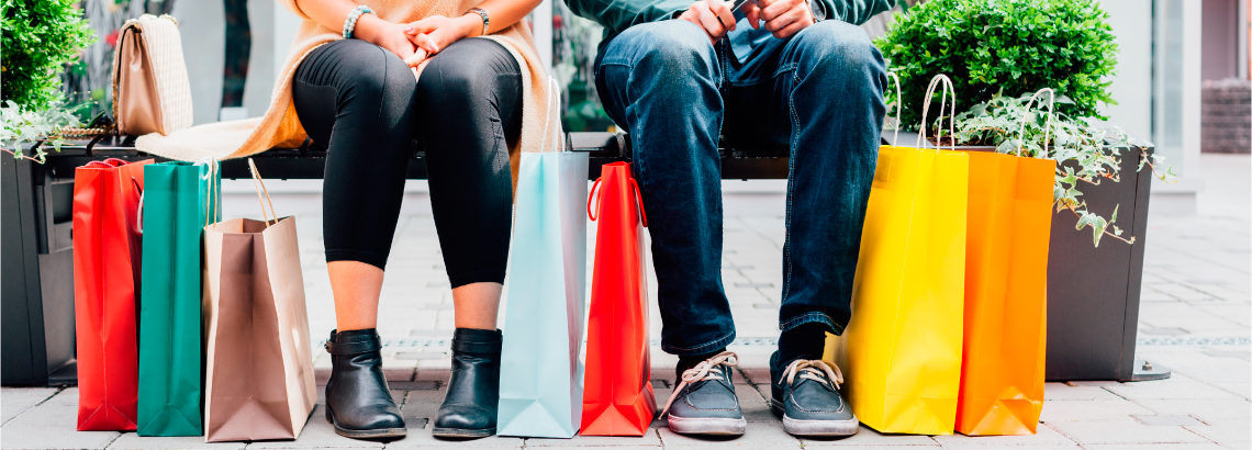 Photograph of 2 people sitting on a bench with shopping bags at their feet.