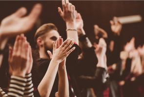 Photograph of an audience applauding, focussing on clapping hands.
