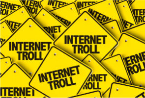 pile of yellow diagonal shaped road signs, each saying 'Internet Troll'
