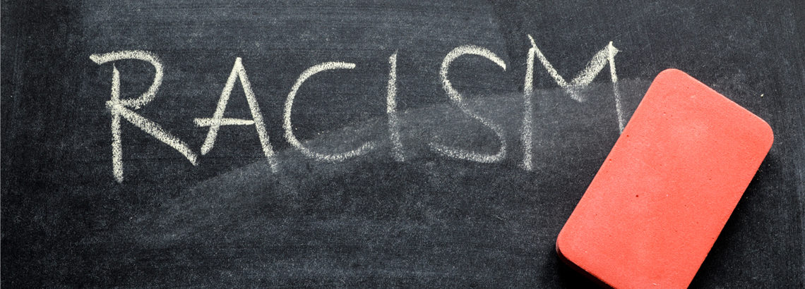 Word 'RACISM' written on a blackboard in white chalk, being erased by a red eraser