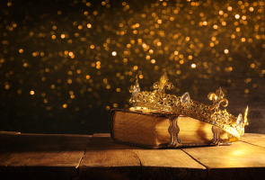 Photo of a wooden table against a dark background with gold coloured diffuse lights. On the table is an old book with metal clasps and resting on this at an angle is a gold crown.