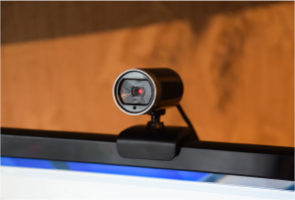 Photograph of a web camera with a red light, attached to the top of a computer monitor
